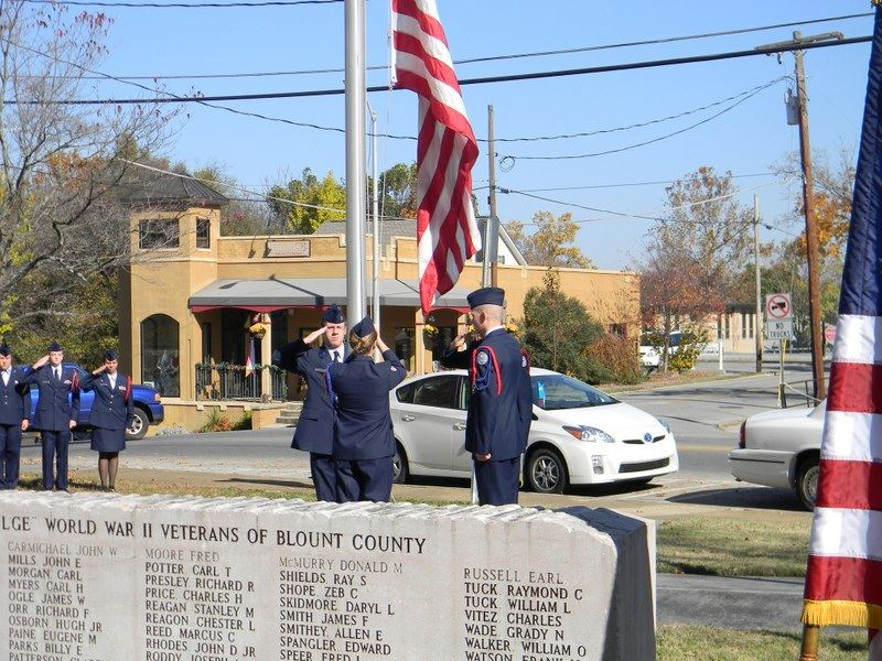 Three cadets salute the American flag as it is raised on pole